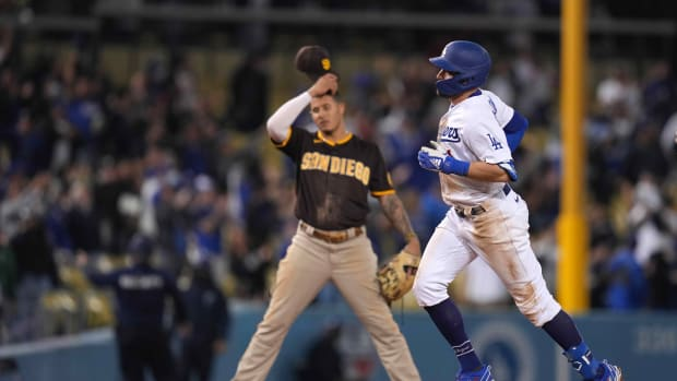 Sep 29, 2021; Los Angeles, California, USA; Los Angeles Dodgers left fielder AJ Pollock (right) rounds the bases after hitting a solo home run in the eighth inning as San Diego Padres third baseman Manny Machado (left) watches at Dodger Stadium. Mandatory Credit: Kirby Lee-USA TODAY Sports